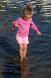 Girl Walking In Water. A young girl walks in shallow water near the shoreline on a bright, sunny day.  Health note: Wearing lite-weight, long-sleeved clothing Royalty Free Stock Images