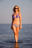 Girl walking from the water. Blonde girl with dark glasses walking from the water Royalty Free Stock Image