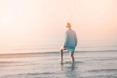 Girl walking in the water. Girl in blue summer dress walking in the sea stock photos