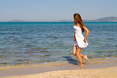 Girl walking on a white sandy beach Stock Photos