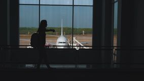 Girl walking at the window in the airport terminal.  stock footage