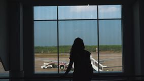 Girl walking at the window in the airport terminal.  stock video