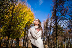 Girl walking in windy autumn park over blue sky Stock Images