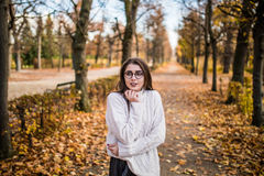 Girl walking in windy autumn park Royalty Free Stock Photo