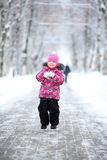 Girl walking in a winter park in snow Royalty Free Stock Image