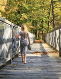 Girl walking on wooden bridge Royalty Free Stock Photos