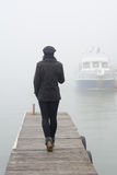 Girl walking on wooden dock on misty autumn day and boat Royalty Free Stock Image
