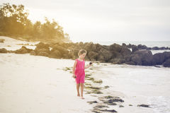 Girl walks alone along the shore of the Indian ocean and collect Stock Photo