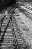 Girl walks alone on railroad tracks, black and white Royalty Free Stock Photos