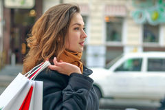 Girl walks along a city street with shopping bags Royalty Free Stock Images