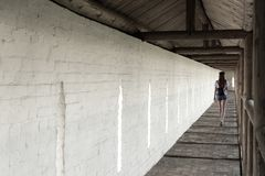 The girl walks along the long aisle of the monastery against the background of a white wall stock images