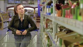Girl walks along wholesale shelves and taking goods in shop trolley, beautiful young wife shopping in a supermarket stock video footage