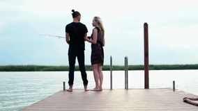Girl walks along wooden pier to her boyfriend, man standing and fishing at lake, beautiful landscape stock footage