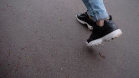 The girl walks around the city on the wet asphalt. Close-up of the girl`s feet stepping on the ground. Slow playback. stock footage