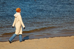 Girl walks on autumn beach in coat and jeans Royalty Free Stock Photography