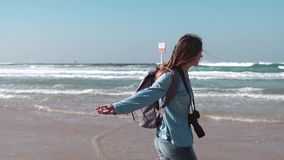 Girl walks along sea shore, throws stone in water. Freedom concept. Wind blowing in hair. Enjoying vacation. Slow motion. Girl walks barefoot along sea shore stock video footage