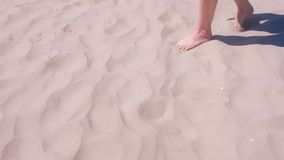 Girl walks barefooted on sand at sea beach resting on vacation, feet in sand. stock video