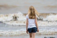 Girl walks on the beach. Girl enjoys her walk along in the beach Royalty Free Stock Image