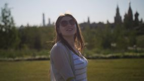 Happy girl enjoys a walk in urban green park. stock footage