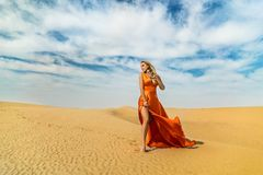 Girl walks on desert. Beautiful woman is walking, staing on sand or dune, touches, shows her legs. Blonde lady in. Dress under blue sky royalty free stock image