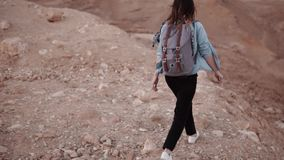 Girl walks on a desert sheer drop. Slow motion. Young woman wanders on big chasm rocks and stones. Dangerous risky path. Girl walks on a desert sheer drop. Slow stock video