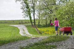 Girl walks down spring lane with flower and wagons Stock Images