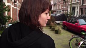 Girl walks down the street in Amsterdam. slow motion. Girl walks down the street in Amsterdam stock footage