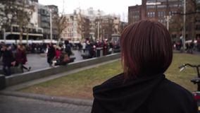 Girl walks down the street in Amsterdam Rembrandtplein. slow motion. Girl walks down the street in Amsterdam. slow motion stock footage