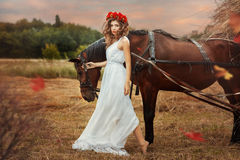 Girl walks into the field with a horse fall. Stock Photography