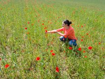 The girl walks on the field with poppies and admires the small red flowers royalty free stock images