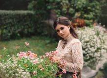 A girl walks in a flowering garden, she has a vintage blouse with a bow, chestnut long hair. she gently cares for her. Flowers. Sweetheart gardener. Artistic Stock Image