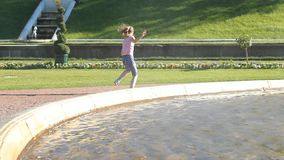 The girl walks by the fountain, plays with water, splashes and rejoices. A sunny day, fountains in Peterhof stock video footage