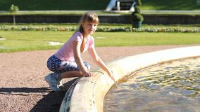 The girl walks by the fountain, plays with water, splashes and rejoices. A sunny day, fountains in Peterhof stock video