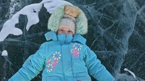 Girl walks on ice. Child on ice in a blizzard. Snow is flying over surface of ice. Snowflakes fly on ice of Lake Baikal. Girl walks on ice. Child on icy in a stock footage