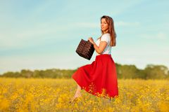 Girl walks on a meadow. A girl walks on a meadow. Meadow of yellow flowers in bloom. On her white T-shirt and red skirt Royalty Free Stock Photography
