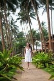 Girl walks among the palm trees. girl resting on the lawn. bride on honeymoon. hotel territory royalty free stock images
