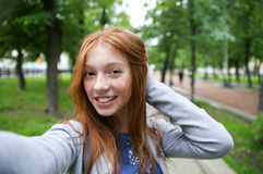 Girl walks in the park and makes selfie. Stock Photos