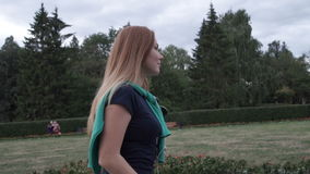 Girl walks in the park. Girl student listening to music and walking in the park stock footage