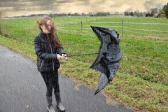 Girl walks through rain and storm, her umbrella is broken. Stormy weather, teenage girl walks outside in the rain fighting with her broken umbrella stock images