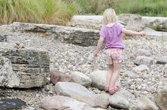 Girl walks on rocks Stock Photography