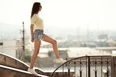 Girl walks on the roof. City at background stock image