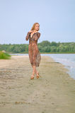 The girl walks on a sandy beach Royalty Free Stock Photos