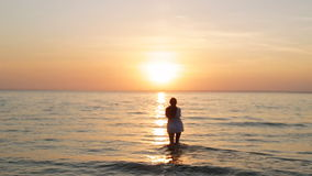 A girl walks into the sea at sunset slow motion. A girl walks into the sea at sunset slo-mo stock video