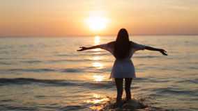 A girl walks into the sea at sunset slow motion. A girl walks into the sea at sunset slo-mo stock footage
