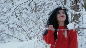 Girl walks through the snowy forest. A young woman happily walks against the backdrop of a beautiful landscape, snow-covered trees. Beautiful curly girl in a red stock footage