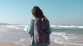 Girl walks on summer sea beach thinking about life. Freedom and retreat concept. Wind blowing in hair. Amazing sky. 4K. Girl with backpack walks on summer sea stock footage