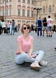 The girl in a pink undershirt and in dark glasses sits on stone blocks at Old Town Square in Prague. royalty free stock photography