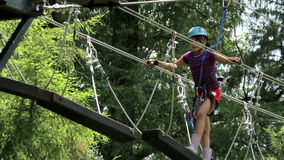 A girl walks through a suspension bridge, she wears an arnes and a helmet. stock video