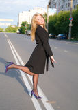 Girl walks on town lonesome road. Royalty Free Stock Photo