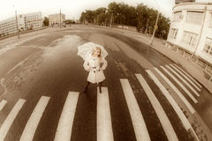Girl walks on town lonesome road. Stock Photos